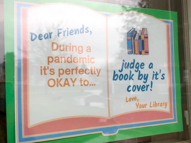 "A sign posted behind a window that reads ""Dear Friends, During a pandemic it's perfectly OKAY to... judge a book by its cover! Love, Your Library."""