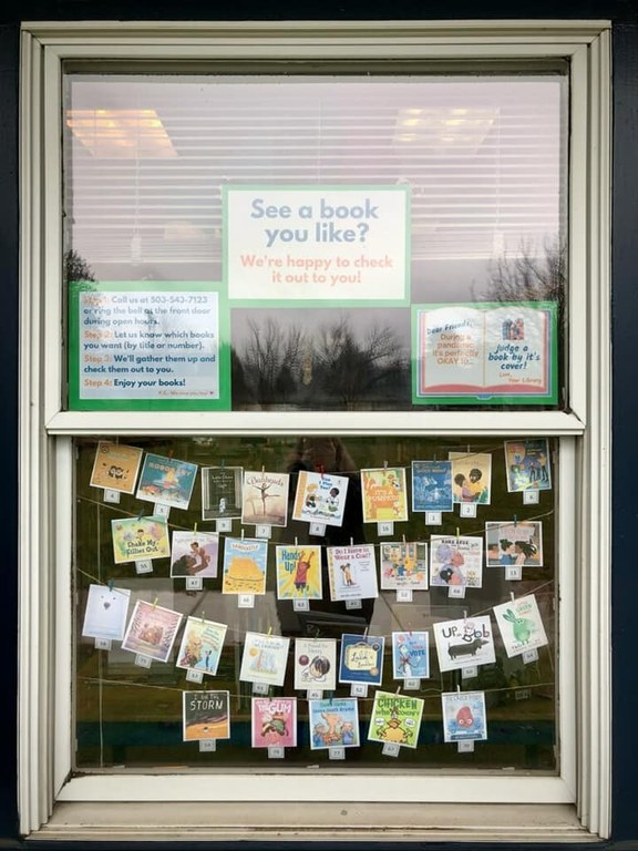 "Three signs in the top window including two pictured here as well as ""See a book you like? We're happy to check it out to you!"" In the bottom window are four rows of picture book covers, each with a number."