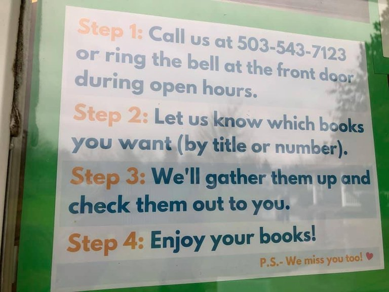 A sign in the window that says: Step 1: Call us at 503-543-7123 or ring the bell at the front during open hours. Step 2: Let us know which books you want (by title or number). Step 3: We'll gather them up and check them out to you. Step 4: Enjoy your books! P.S. - We miss you too! Heart Shape.